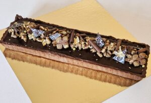 Rectangular chocolate tart with chocolate sablé crust, chocolate cookies, chocolate curls and gold dusted caramelized pecans