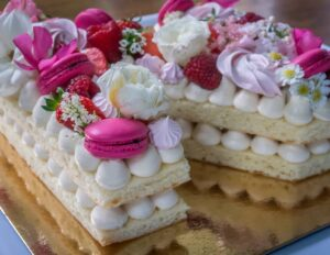 Letter cake with meringues, macarons and fresh fruit and flowers