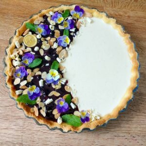 Panna Cotta tart with blueberry sauce, caramelized peanuts, white chocolate curls and violets