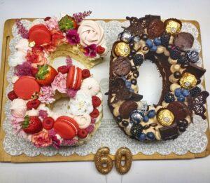 Dual birthday cake for a grandmother's 60th birthday and her granddaughter's 9th birthday. Vanilla cake with Vanilla buttercream, fresh fruit and flowers, raspberry macarons and meringues. Chocolate cake and buttercream with brownies, fresh fruit, chocolate and chocolate butterflies.