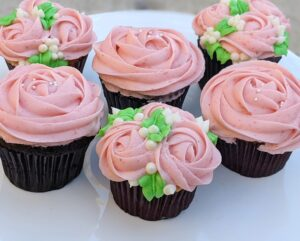 Chocolate and Vanilla cupcakes with a strawberry jelly filling and fresh strawberry buttercream rose design.